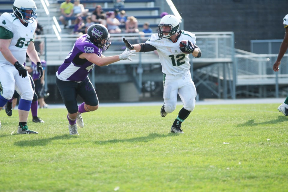 Airdrie Irish running back Connor Lutz puts up a stiff arm against a Wolfpack linebacker June 1. Photo by Scott Strasser/Rocky View Publishing