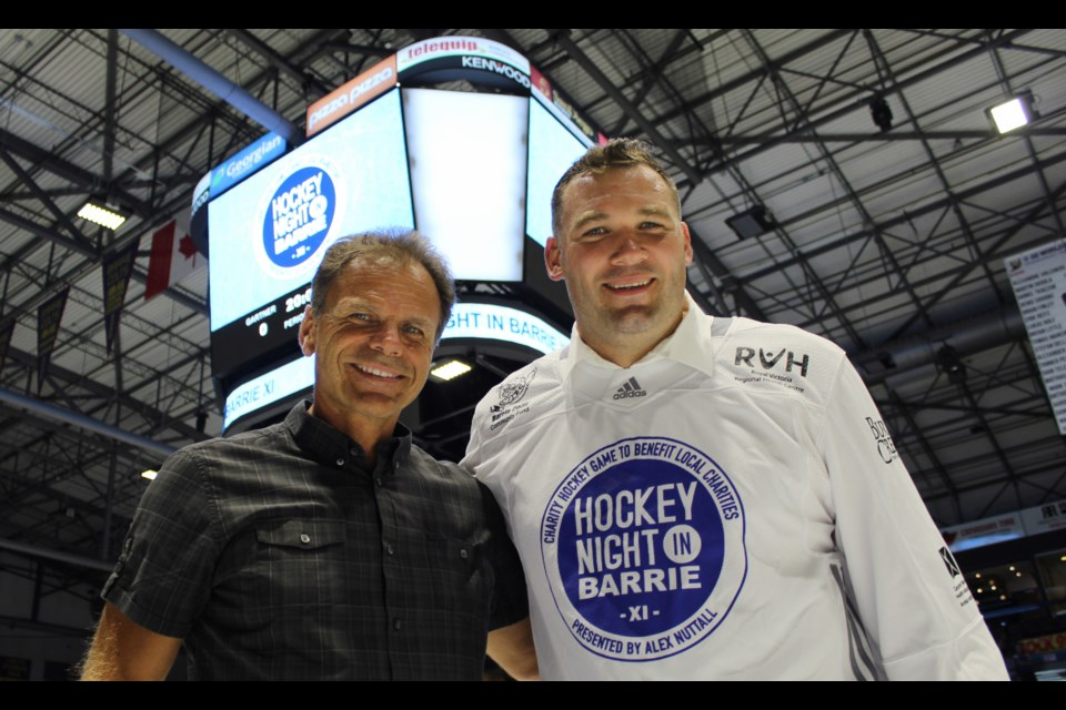 Local MP Alex Nuttall, right, poses with Hockey Hall of Famer Mike Gartner near centre ice at the Barrie Molson Centre. Raymond Bowe/BarrieToday