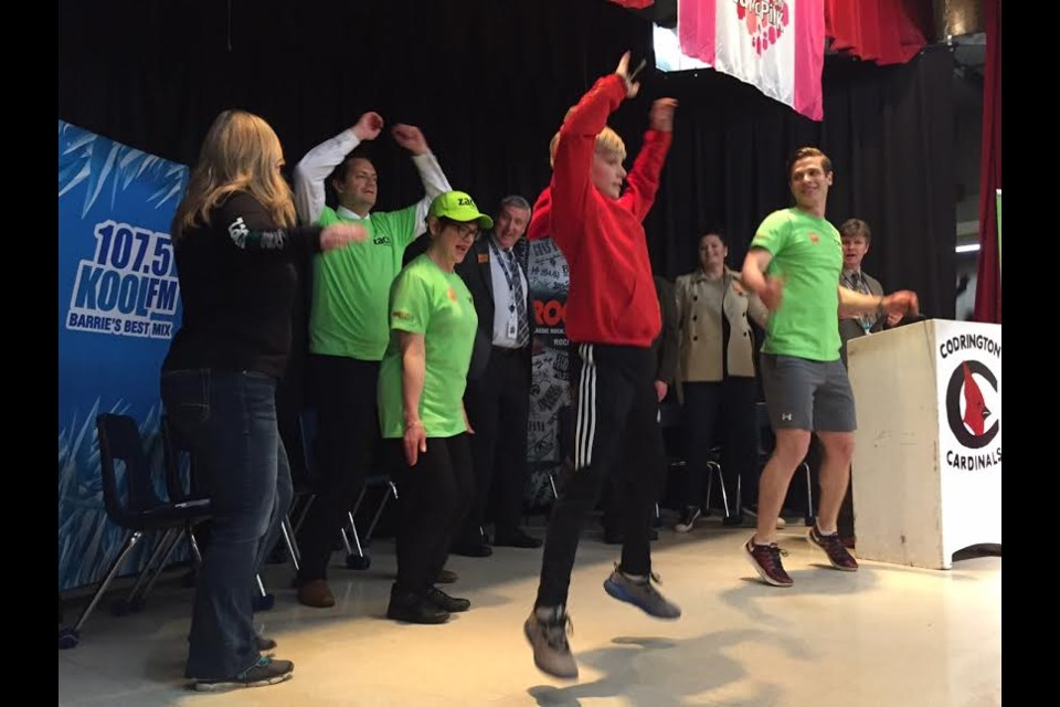 Zach Hofer helps his schoolmates warm up at the official launch of his Zach Makes Tracks fundraising run. 