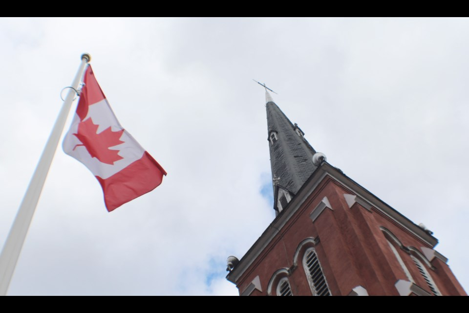 The Canadian flag flies outside Collier Street United Church in downtown Barrie. Collier Street will be one of four Barrie churches taking part in the Bells of Peace on Sunday. Raymond Bowe/BarrieToday