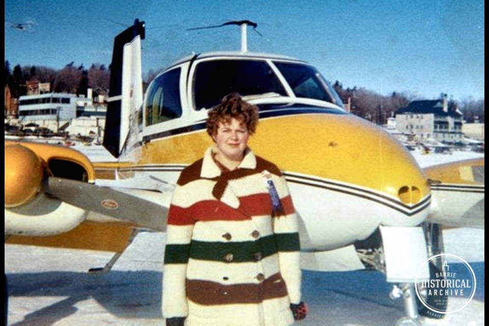 A woman posing with a plane during the 1968 Winter Carnival. Photo provided by Barrie Historical Archive