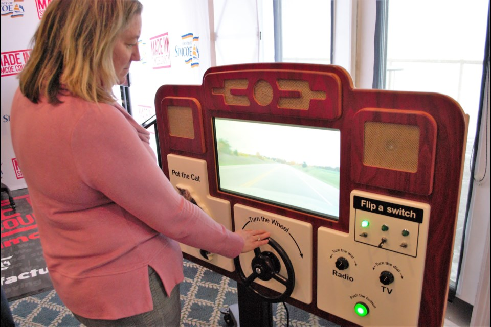 Michelle Cooper, senior account manager at BDC in Barrie, tests out ABBY, a device that offers ambient experiences for dementia patients, Wednesday. ABBY is manufactured by Ambient Activity in Midland. Jessica Owen/BarrieToday
