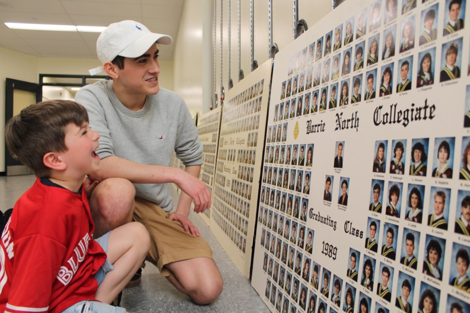 Six-year-old Finn Armatage and his 16-year-old brother, Walker, take a look at their father's graduation picture from 1991 at Barrie North Collegiate, Wednesday evening. Raymond Bowe/BarrieToday