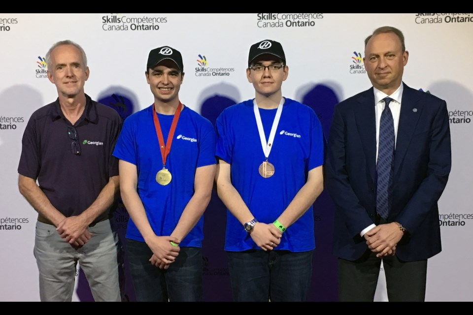 Georgian College CNC Precision Skills students Andrew Pittman, second from left, won gold at the Skills Ontario competition May 3. Teammate Augusto Marzinotto won bronze. Accompanying them are faculty coach Jurgen Hierholzer, left, and Dan Ferko of the Gene Haas Foundation, a generous donor to Georgian's CNC program.