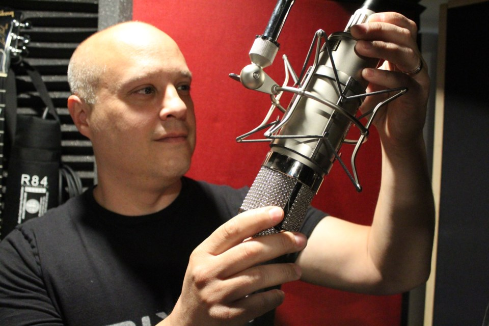 Daryl Sarnat, the owner and lead engineer of Mix 11 Studios in Barrie, adjusts a microphone in the vocal booth. Raymond Bowe/BarrieToday