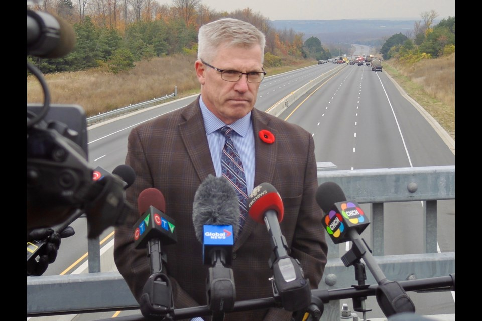 OPP Commissioner Vince Hawkes stands on an overpass with the scene of Tuesday's massive fireball collision in the background on Highway 400.