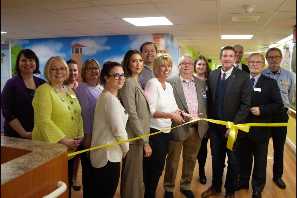 Sandie Collins (centre) cuts the ribbon on the newly designed dementia care wing at IOOF Seniors Home in Barrie. Jessica Owen/BarrieToday