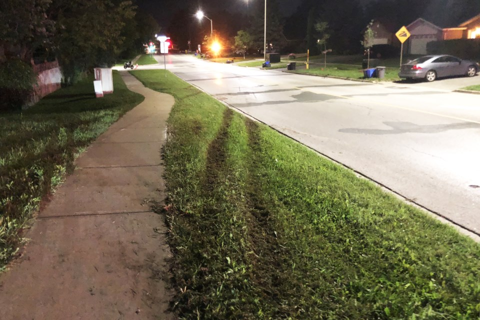 Marks left in the grass show where a Tesla lost control and left the road prior to coming to rest at Assikinack Public School after it jumped the steep railroad crossing on Little Avenue at 8:30 p.m. on Aug. 28, 2018. Kevin Lamb for BarrieToday