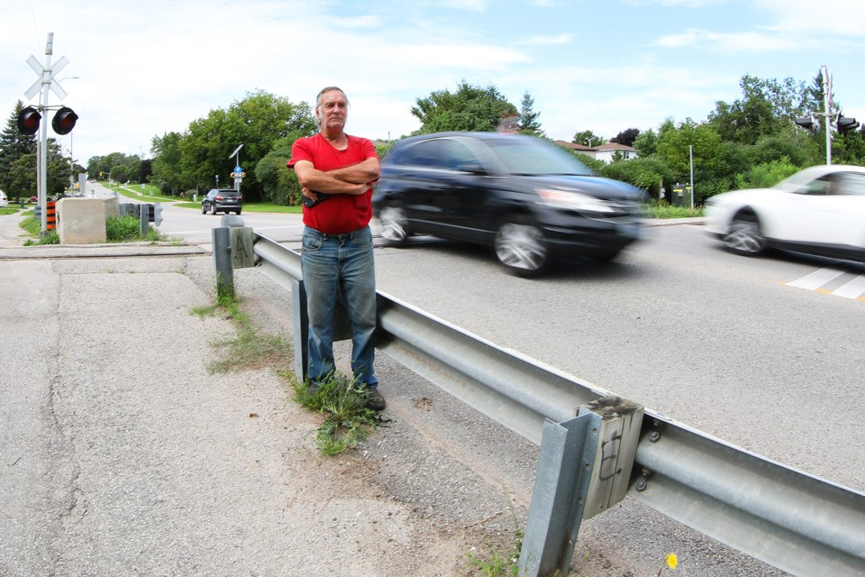Concerned resident Roger Natale watches vehicles climb the steep grade leading up to railroad tracks on Little Avenue in south-end Barrie where a Tesla launched iinto the air Tuesday night before crashing in the parking lot of Assikinack Public School. A 46-year-old man has been charged. Kevin Lamb for BarrieToday