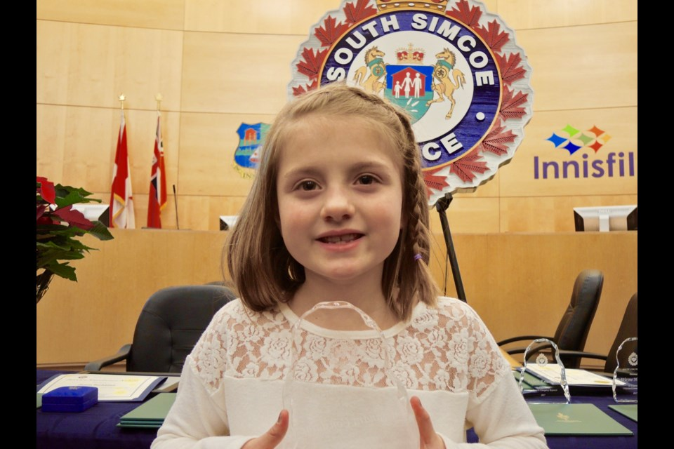 Cassandra Considine, 7, holds her Citizen Award following a ceremony Thursday night in Innisfil.