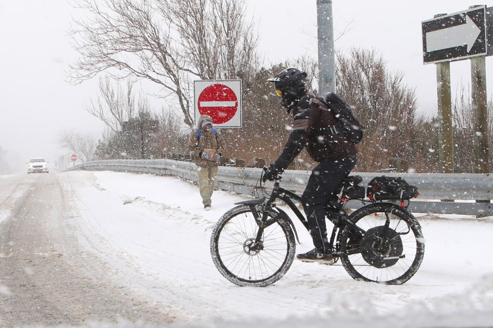Life continues on as somewhat normal as a cyclist fights through thick slush on Bayfield street in Barrie during an ice storm on Saturday, April 14, 2018. Kevin Lamb for BarrieToday.