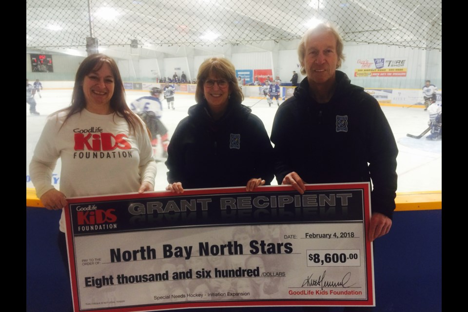 Mariane Wagner presents a cheque from the GoodLife Kids Foundation, to North Bay North Stars President Sharon Fung, and Head Coach David Nadeau to expand their hockey program.