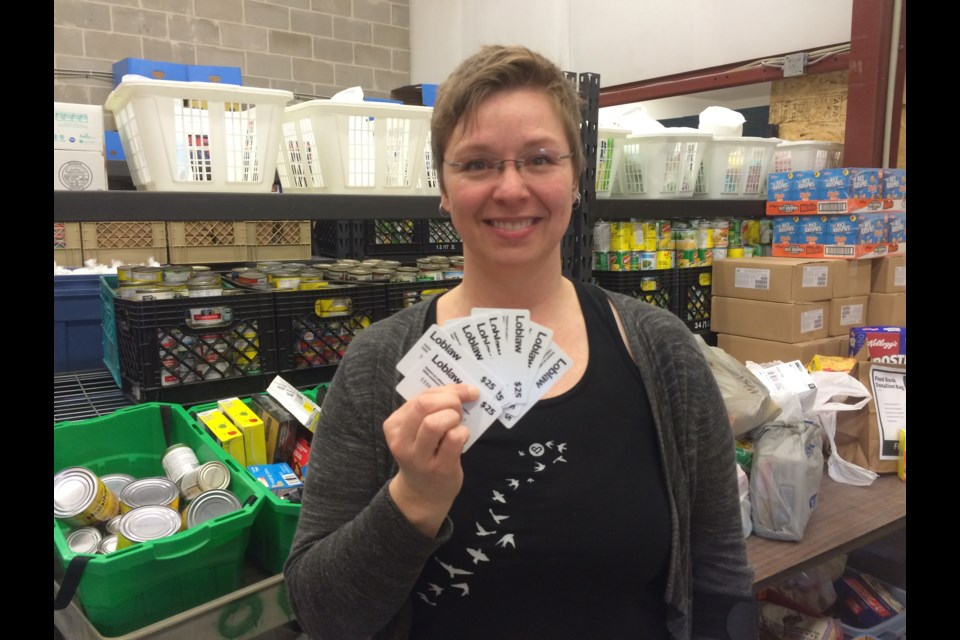 North Bay Food Bank Manager Amber Livingstone holds up donated Loblaw rebate cards.