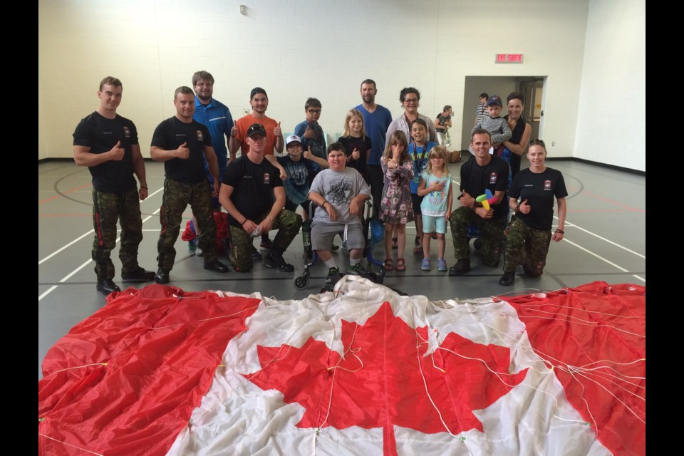 Members of the Canadian Armed Forces Skyhawks parachute team drop in to One Kids Place Treatment Centre