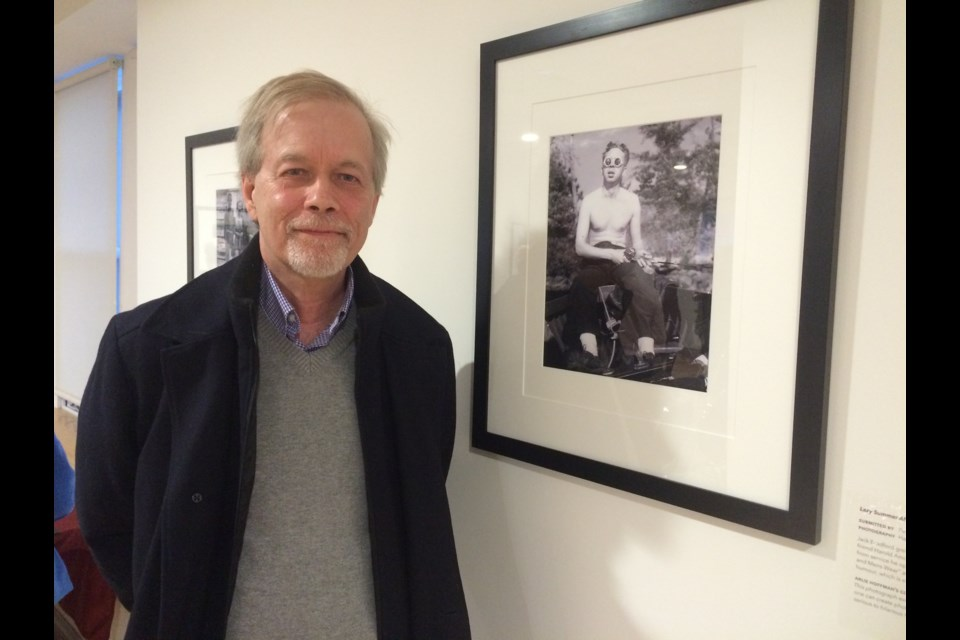 Peter Amos stands beside a picture of a young Jack Bradford, a picture he submitted for the Coming of Age exhibit at the North Bay Museum.