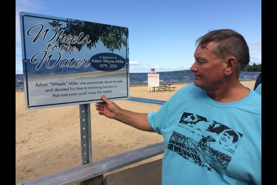 """North Bay's first beach accessibility mat was dedicated in honour of Adam """"Wheels"""" Miller who worked tirelessly to get a mat for North Bay. His father Wayne gently touches the sign which bears his son's name, located beside the mat at Marathon Beach."""