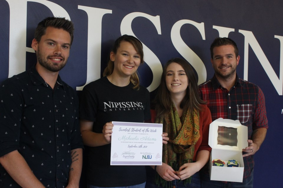 John and Nathan Serran, owners of SugarDaddy Cupcakes & Catering, presenting Michaela Adams, winner of Sweetest Student of the Week with a certificate and cupcakes, as well as Emily Prevost who nominated her. Photo by Ryen Veldhuis.