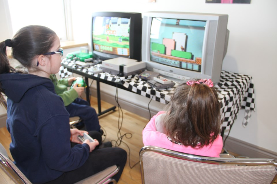Isabelle Thomas plays Super Mario on an old Nintendo video game console as part of the Retro Video Game event at Discovery Museum.  Photo by Chris Dawson.
