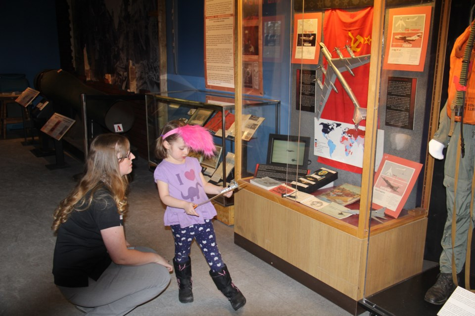 Curatorial Assistant Bethany Aitchison helps Evelyn Craig, 4, with the scavenger hunt at the Museum of Aerospace.