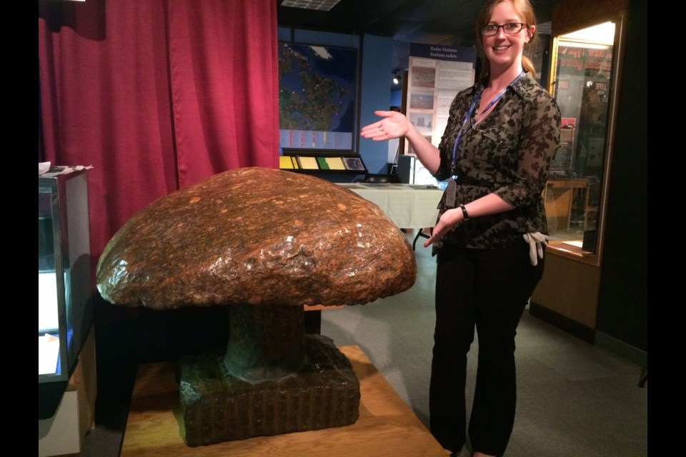 Bethany Aitchison shows of the giant granite mushroom. The mascot of NORAD workers who served in 'The Hole'. Photo by Jeff Turl.