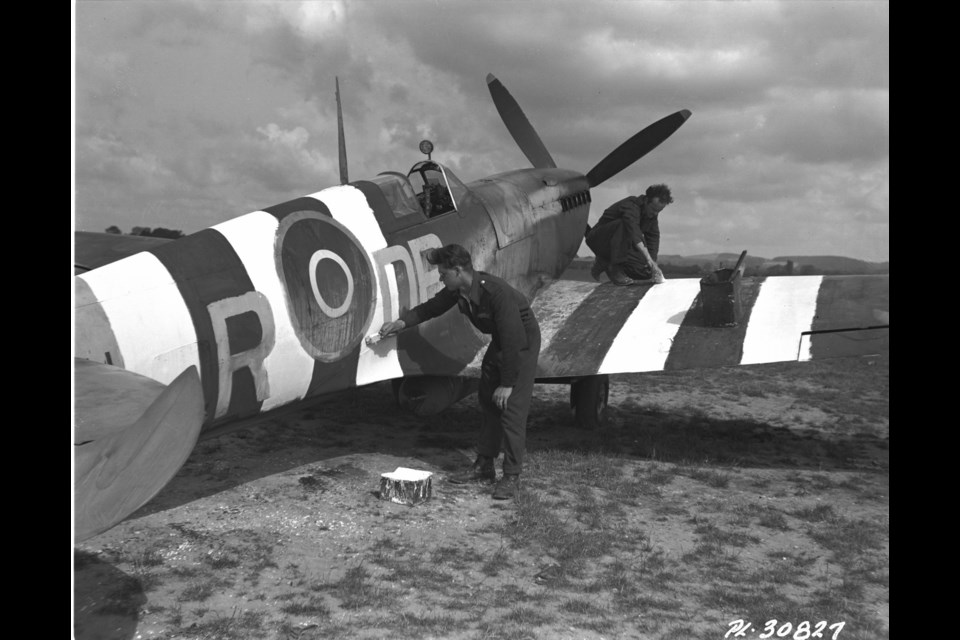 These two RCAF boys had a large job on their hands, painting the black and