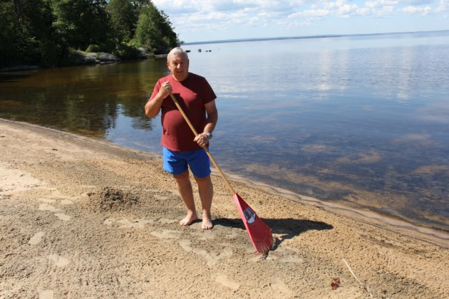 USED 170706 1 Brian Baldwin rakes up piles of dead shad flies on his beach. Lake Nipissing. Photo by Brenda Turl for BayToday.