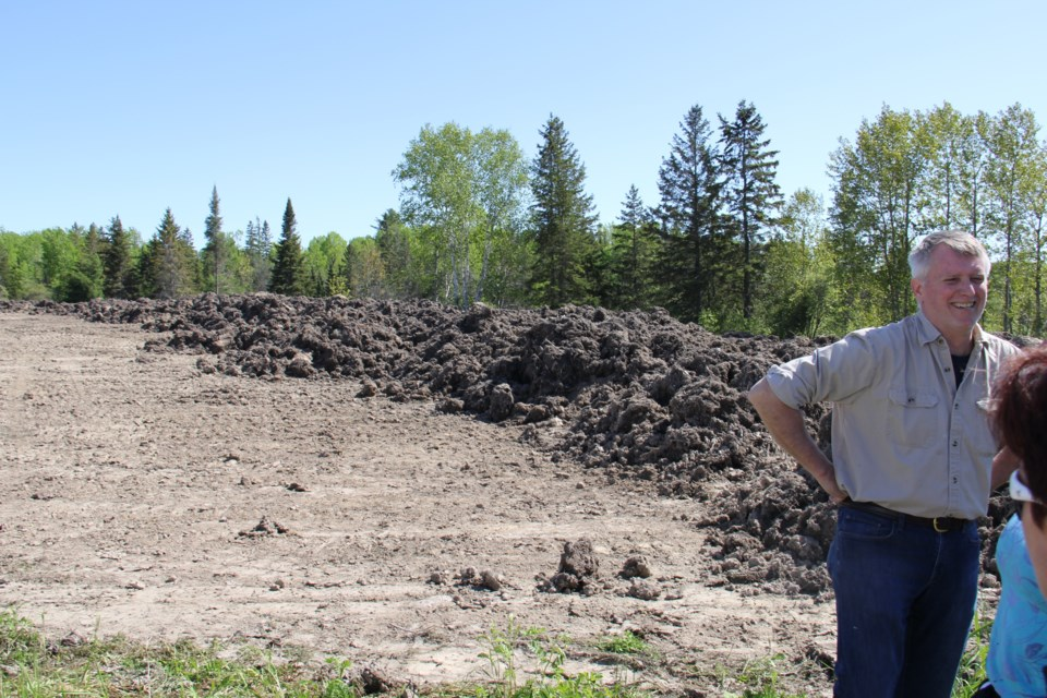 Land surveyor Paul Goodridge stands in front of the mounds of soil from the casino site that has been dumped on a property nearby. Jeff Turl/BayToday.