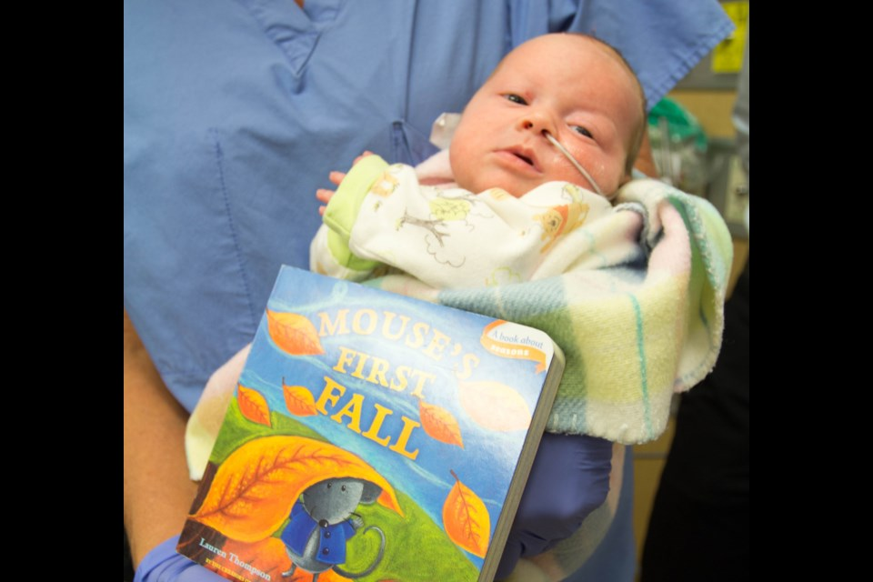 Baby Emille O'Reilly with one of the new books from the lending library. Submitted.