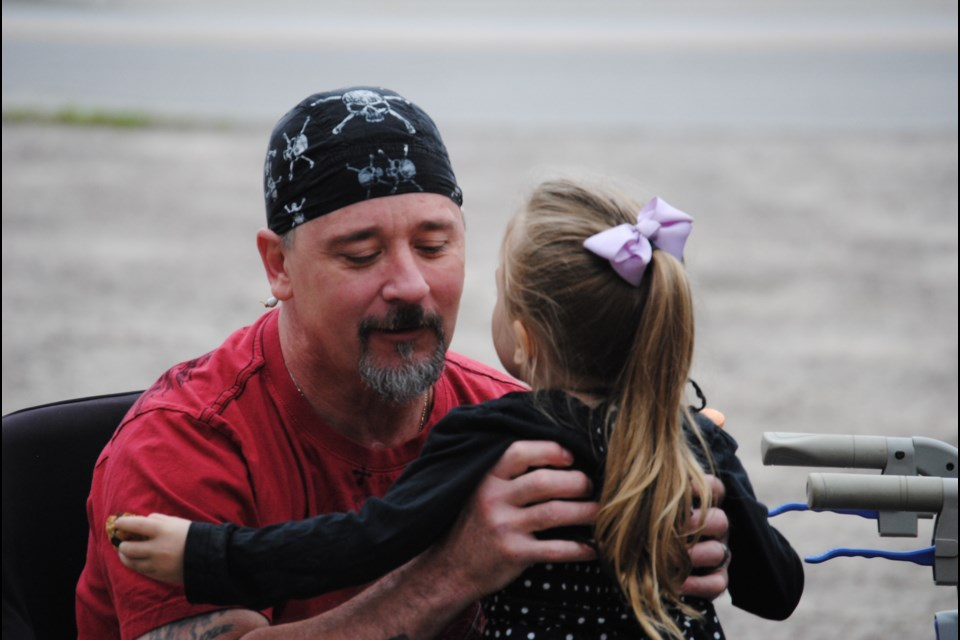 Brad Martin, victim of a Lakeshore Drive collision ten months ago, is welcomed at a party in his honour by his granddaughter, Sunday. Photo by Stu Campaigne.
