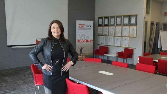 Sue Symons shows off the former gymnasium — now a training room and space for community gatherings — at the repurposed elementary school that's now the new office for Royal LePage North Bay Real Estate Services. (Lindsay Kelly photo)