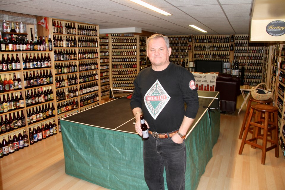 Tony Matheson stands in front of his massive full beer bottle collection.  Photo by Chris Dawson.