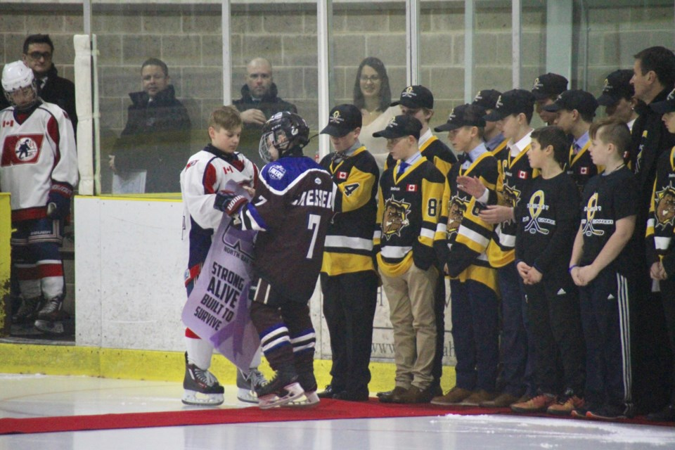Nolan Newton hands over a purple Trappers banner to cancer survivor Brock Chessell of the Huron-Perth Lakers.   Photo by Chris Dawson.