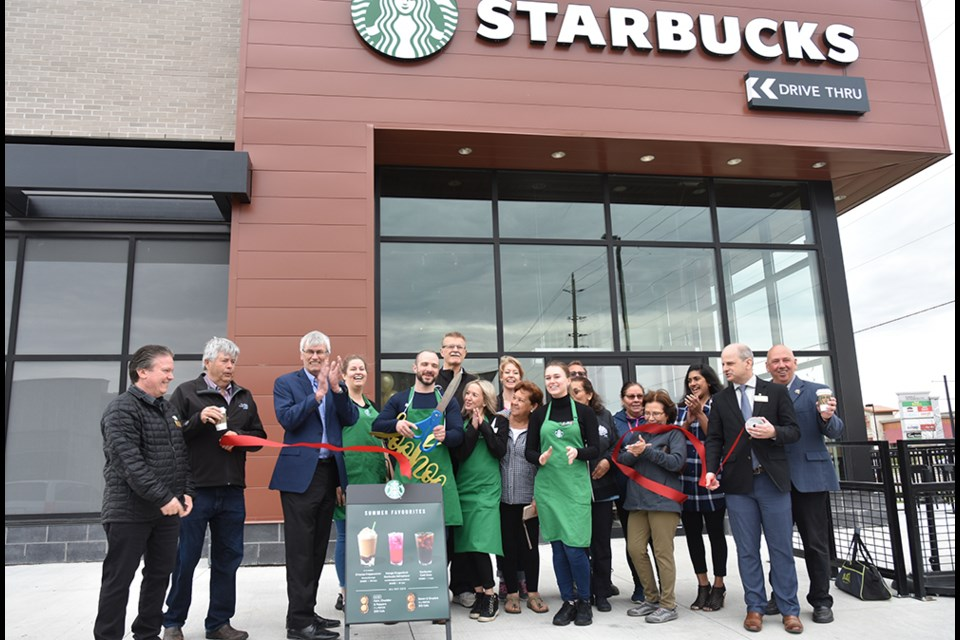 Staff, customers, Mayor and Councillors cut the red ribbon, officially opening Bradford West Starbucks on May 22. Miriam King/Bradford Today