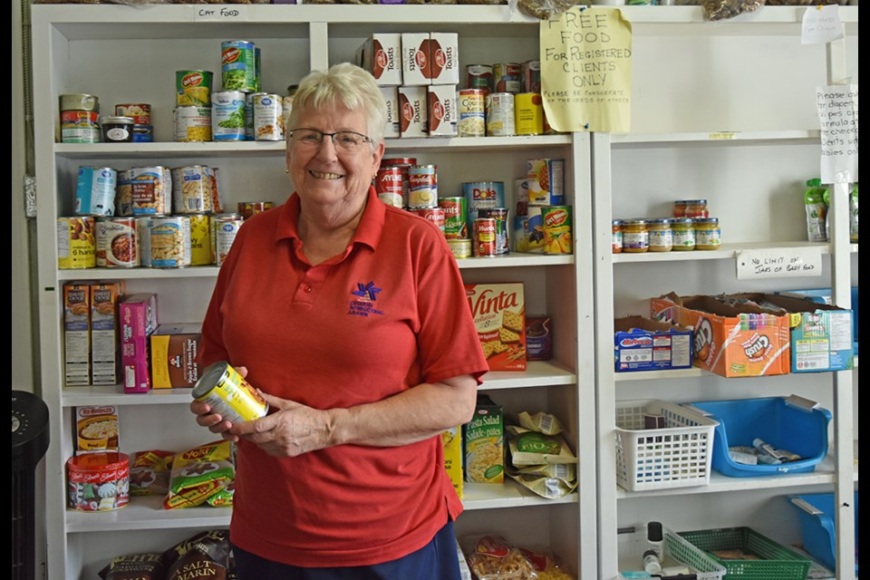 Anne Silvey, volunteer president of the Helping Hand Food Bank in Bradford, checks the best-before date on a can, before setting it on the free shelf at the food bank. Miriam King/BradfordToday