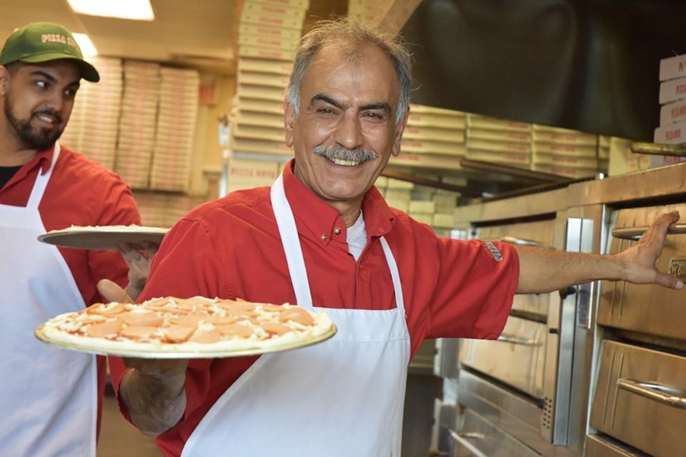 Serving up medium pepperoni pizzas at Pizza Nova, to raise money for Variety Village. Miriam King/Bradford Today