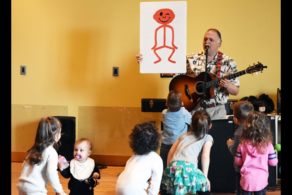 Kids match the pose of the stick figure held up by singer Russ Clayton, at the library. Miriam King/Bradford Today