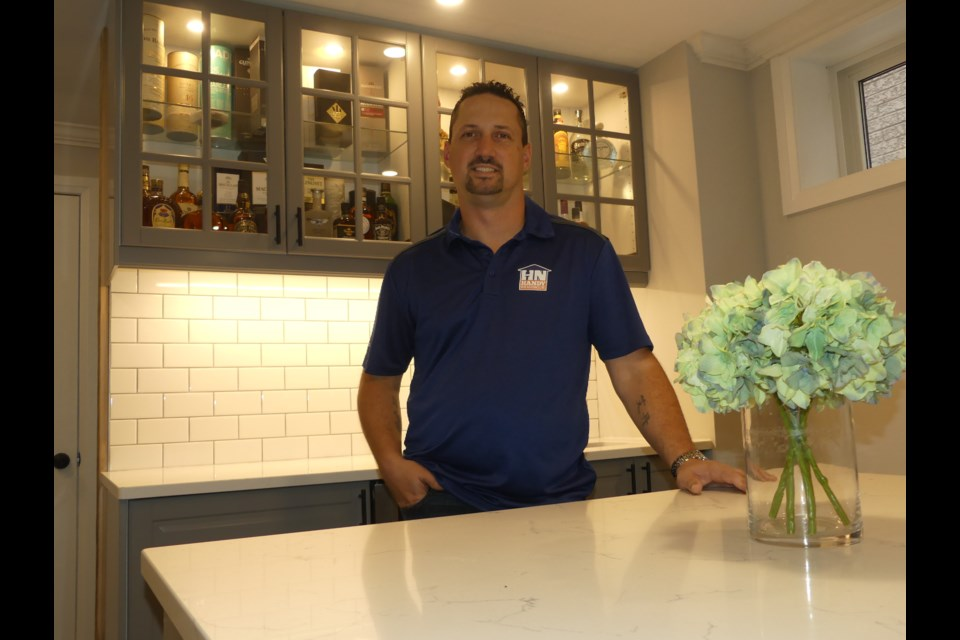 Jason Farrugia, standing in a basement bar area he built himself, started Handy Neighbour for Hire nearly four years ago.  Jenni Dunning/BradfordToday