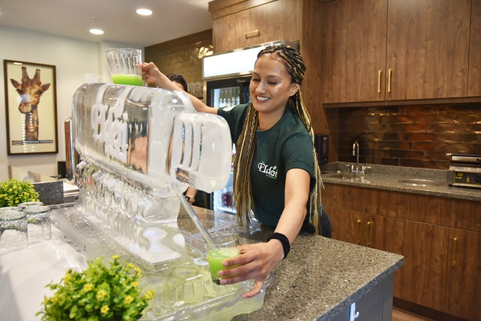 Karen Rivera serves up a non-alcoholic mixture of orange juice, Sprite and blue raspberry martini mix at the Bistro, using an ice sculpture to chill the drink. Miriam King/Bradford Today