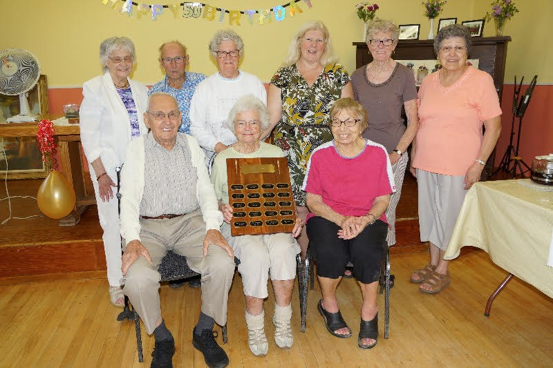 Some of the Happy 60s Bid Euchre Club's members with the restored president's plaque. Submitted photo