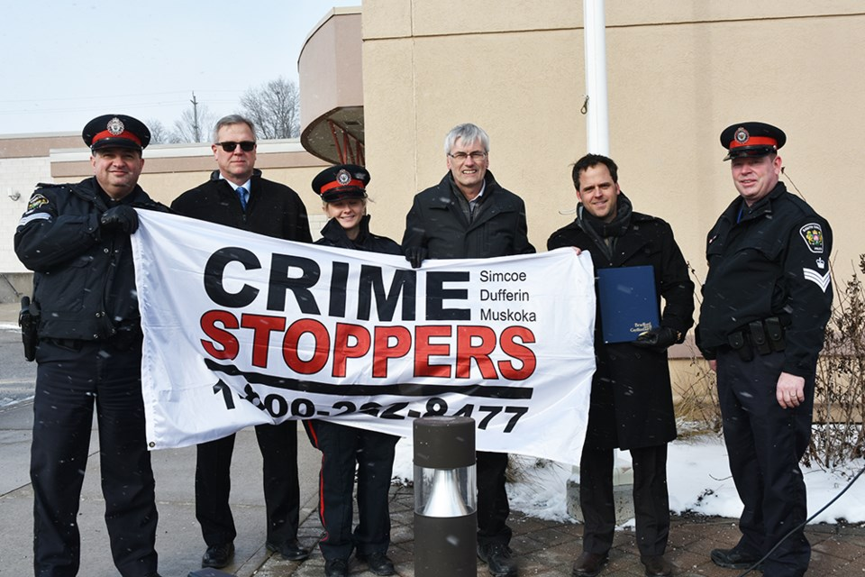 Raising the Crime Stoppers flag from left, South Simcoe Police Sgt. Lew DaSilva, Sgt. Brad Reynolds, Const. Nicole Nielsen, Mayor Rob Keffer, Coun. Peter Ferragine, and Staff Sgt. Steve Wilson, at the Bradford Courthouse, Jan. 10. Miriam King/Bradford Today