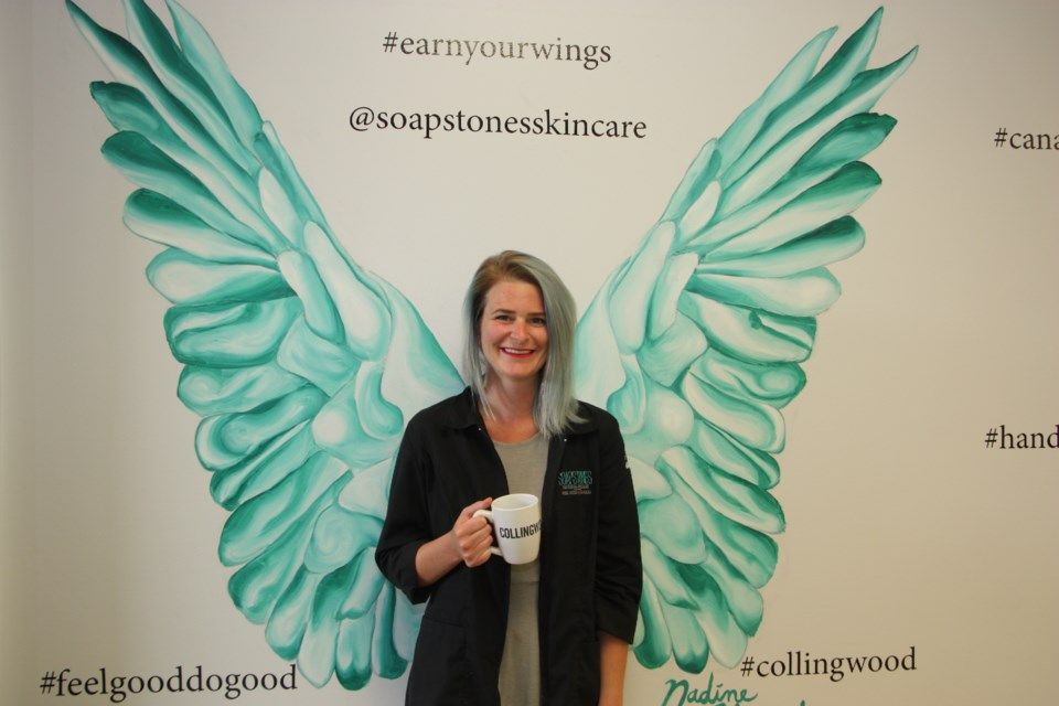 Andrea Crane is the manager at Collingwood Soapstones. She's posing in front of the store's set of wings, meant to help customers feel good about their purchases. Erika Engel/CollingwoodToday