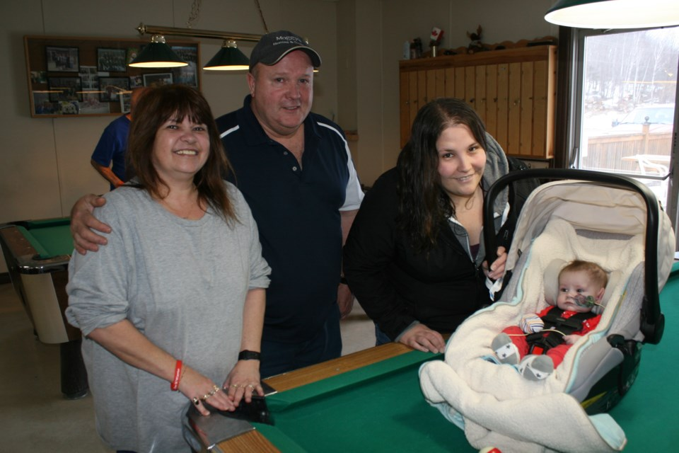 Saturday's nine-ball pool tournament organizers Darin and Joanna Moggy of the Elliot Lake eight-ball pool league, welcome Elijah Hennessey and his mother Jessie to the tournament at the Moose Lodge. The event raised $1,009 for Elijah's ongoing medical treatment. (photo by Kris Svela)