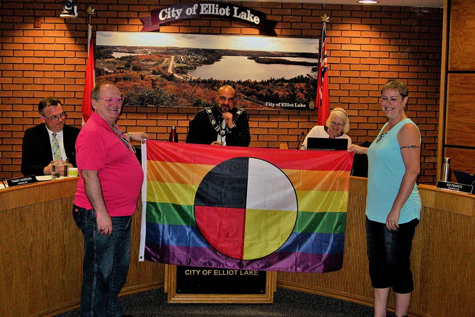 Pride Two Spirit Flag held by Douglas Elliott and Chantal Vaillancourt in Elliot Lake Council Chamber. Brent Sleightholm for ElliotLakeToday