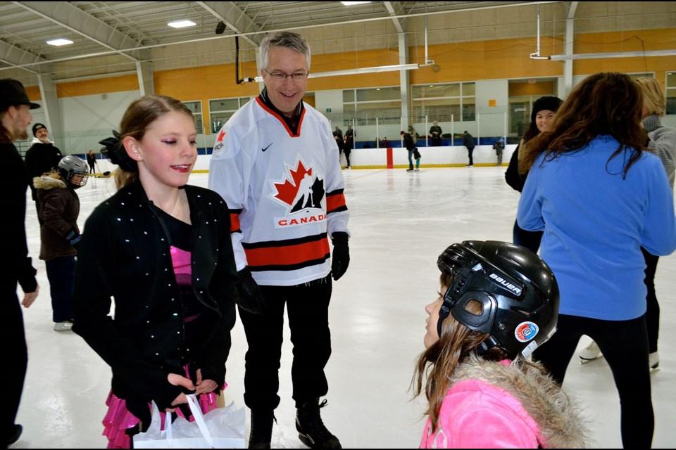 8062fa56b5c Figure skater Audrey Brisbin talks to a young fan as Lloyd Longfield looks  on. Troy