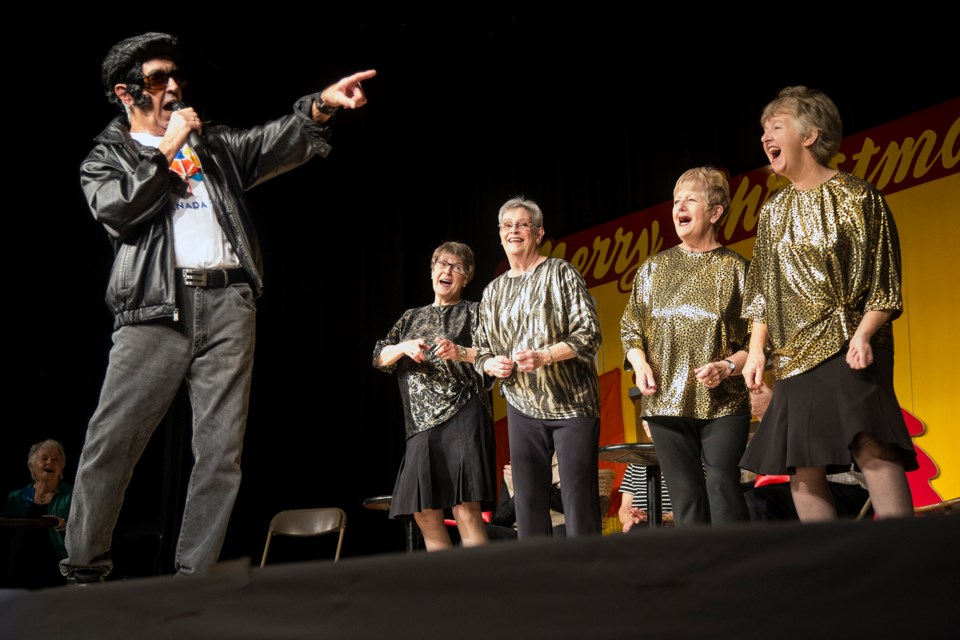 Barry Scott as Elvis performs while Elaine Gowing, Doreen Muir, Judith Preston and Penny Richards (not in order) sing backup during  the Guelph Wellington Seniors Association annual Christmas variety show at Evergreen Seniors Community Centre on Thursday. The revue, titled