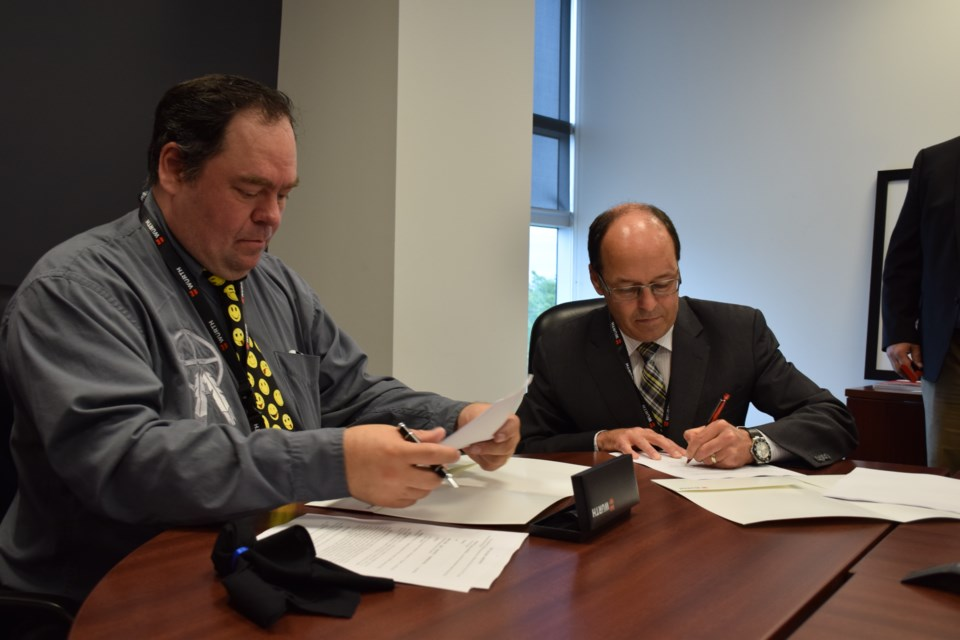 Missanabie Cree First Nation chief Jason Gauthier, left, and Würth Canada CEO and president Ernie Sweeney sign a joint venture agreement to supply north mining operations on the First Nation's traditional territory. Rob O'Flanagan/GuelphToday