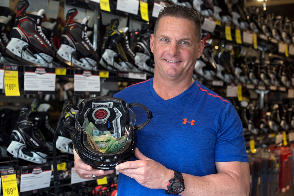 Todd Gumbley, owner of Hockey Shop Source for Sports, holds up a helmet with donations made by customers in support of the victims and families of the devastating bus crash in Saskatchewan. Kenneth Armstrong/GuelphToday