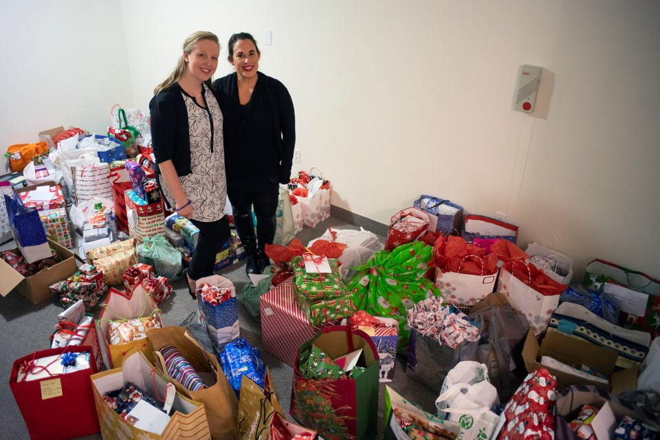 Adopt-a-Senior co-organizers Kayla McQueen and Kyla Rowntree  pose in a room at the Village of Riverside Glen filled with just some of the donations made through the program in its first year. Kenneth Armstrong/GuelphToday