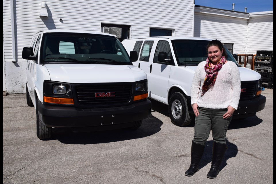 The Guelph Food Bank's Pauline Cripps stands with a pair of nearly new vans the agency was able to purchase thanks for funds from the Walmart Foundation. Rob O'Flanagan/GuelphToday