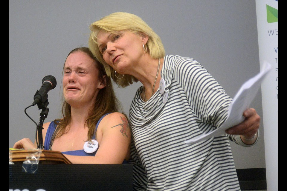 Jenn Schneider, left, recounts her battles with substance abuse with help from Adrienne Crowder of the Wellington-Guelph Drug Strategy during the Stop The Stigma rally at City Hall Friday, Sept. 29, 2017. Tony Saxon/GuelphToday